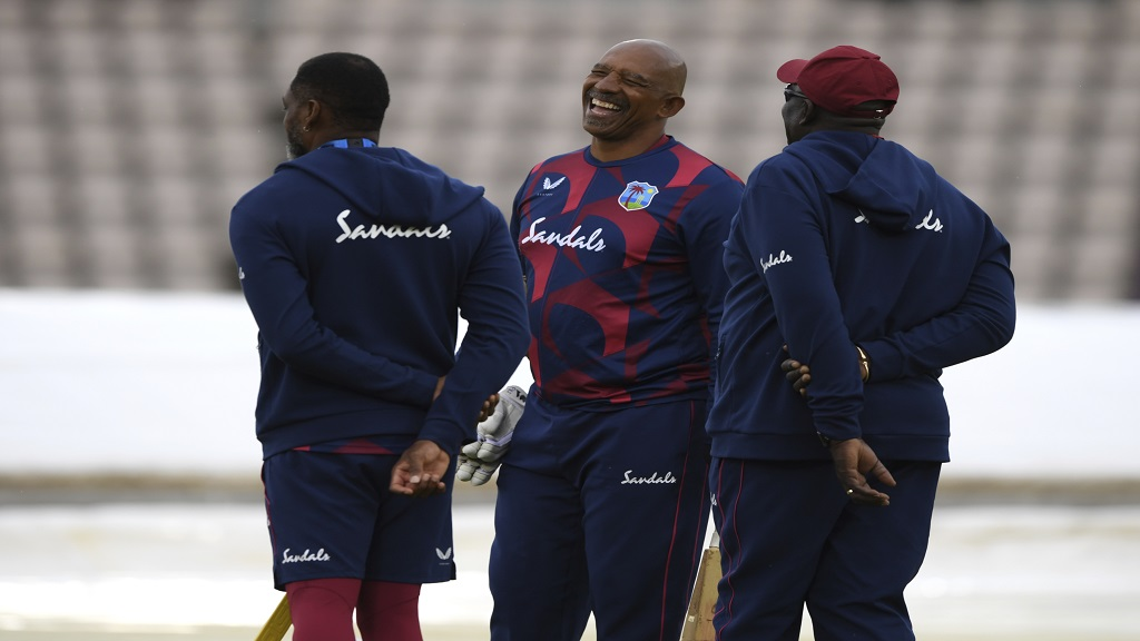 West Indies' team coach Phil Simmons, centre, shares a laugh with members of support staff before the start of the first day of the opening cricket Test match against England, at the Ageas Bowl in Southampton, England, Wednesday July 8, 2020. (Mike Hewitt/Pool via AP).