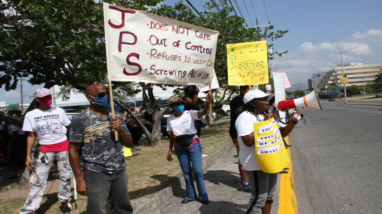 Placard-bearing protesters demonstrating outside the Jamaica Public Service headquarters in New Kingston on Saturday.