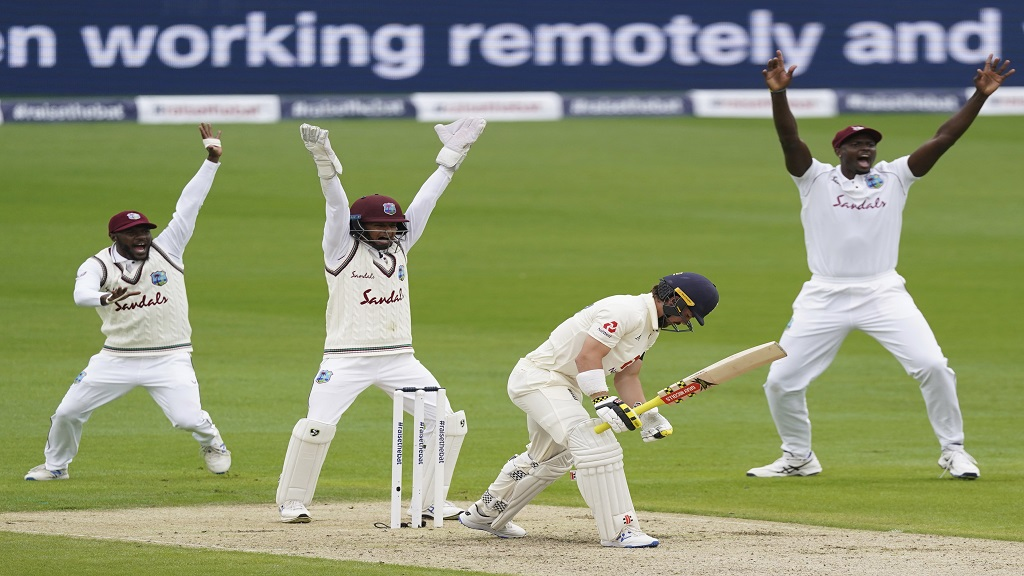 West Indies players appeal successfully for the wicket of England's Rory Burns, second right, during the first day of the second cricket Test match at Old Trafford in Manchester, England, Thursday, July 16, 2020. (AP Photo/Jon Super, Pool).