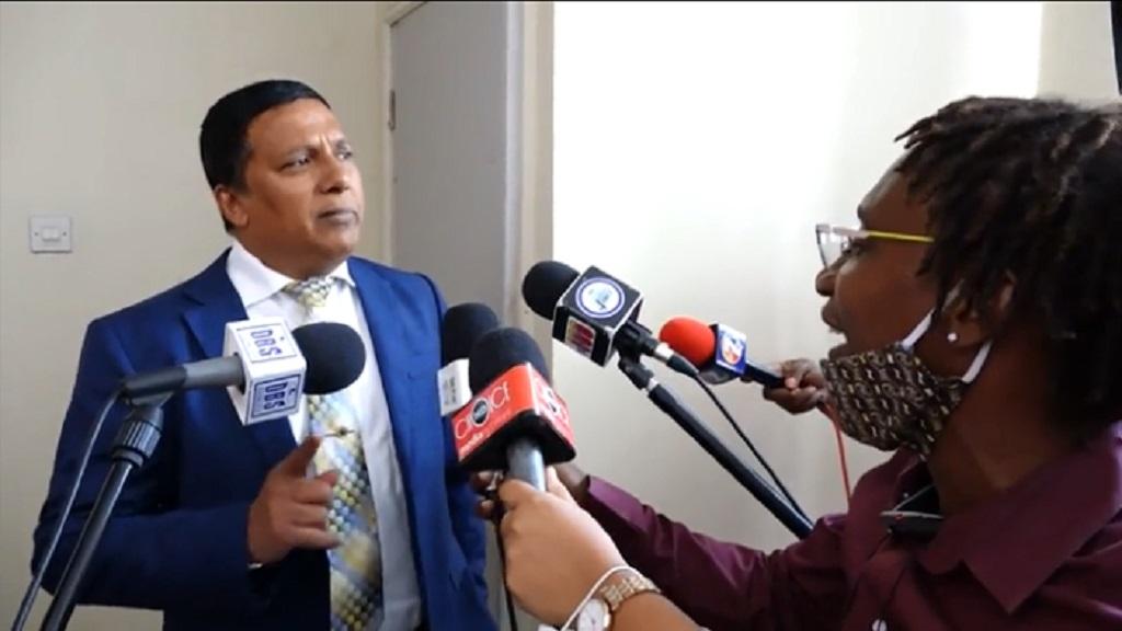 Minister Guy Joseph (left), reporter Miguel Fevrier