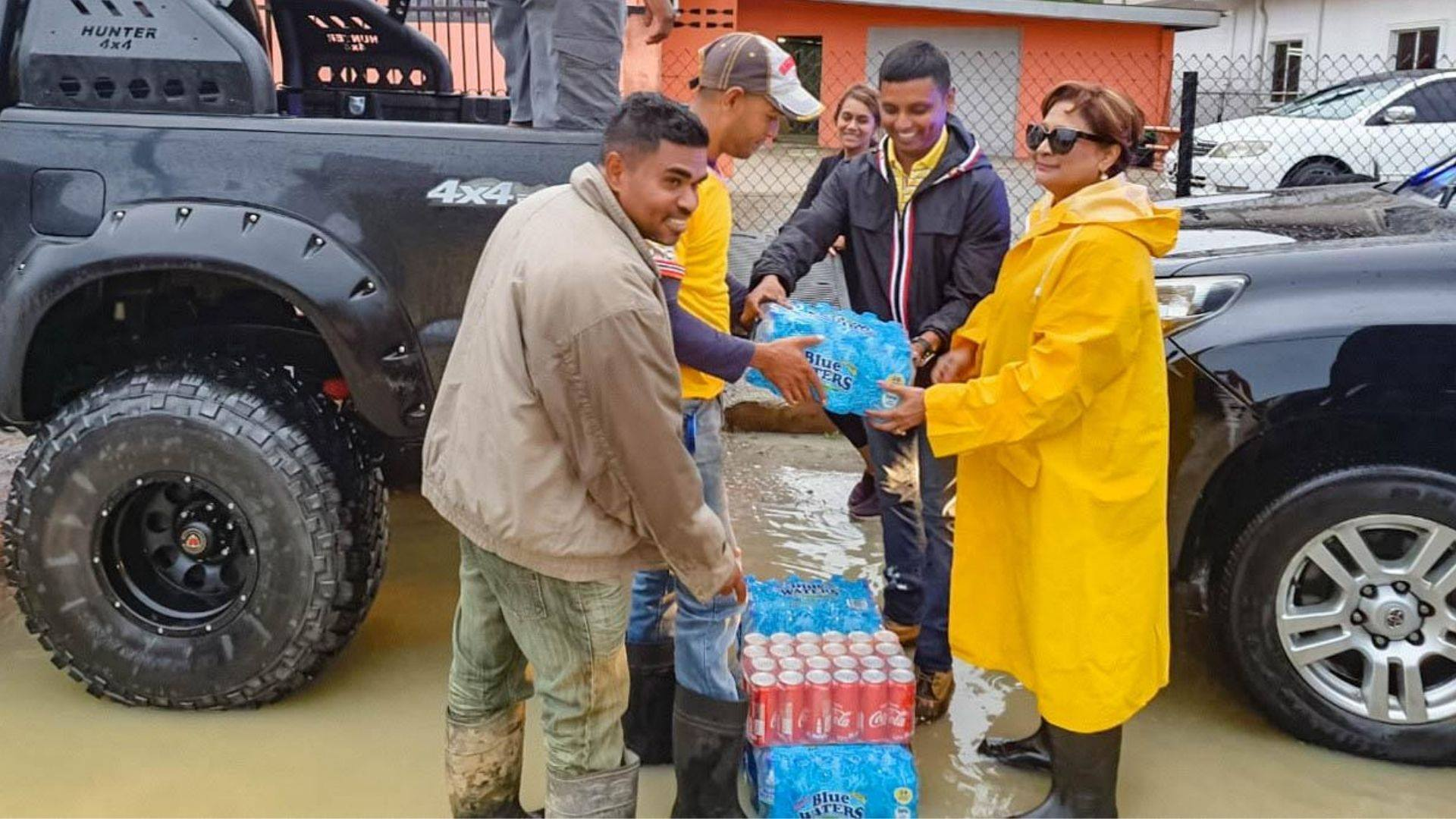 Political Leader of the UNC, Kamla Persad-Bissessar assists in relief supply distribution.