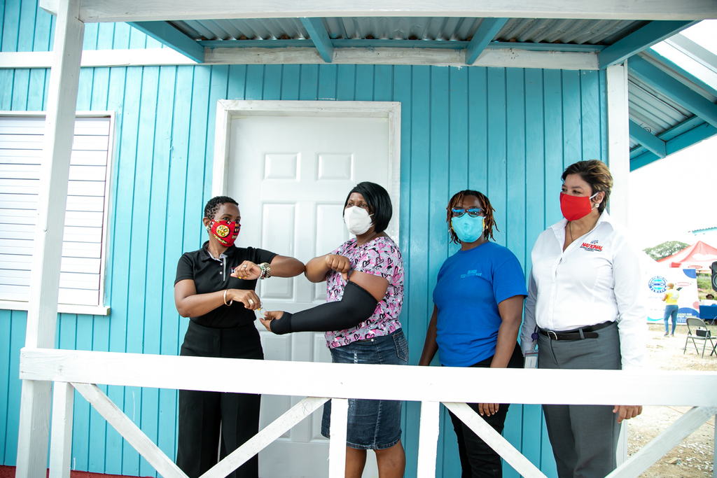 Marvette Johnson (second left) receives the key to her new from a representative from the Housing Agency of Jamaica (first left), Executive Director of Food for the Poor- Kivette Silvera (third left) and Executive Director of National Baking Company Foundation- Christine Scott-Brown (fourth left).