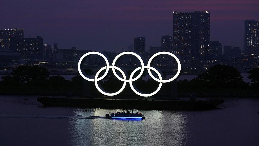 In this June 3, 2020, photo, the Olympic rings float in the water at sunset in the Odaiba section in Tokyo.  (AP Photo/Eugene Hoshiko).