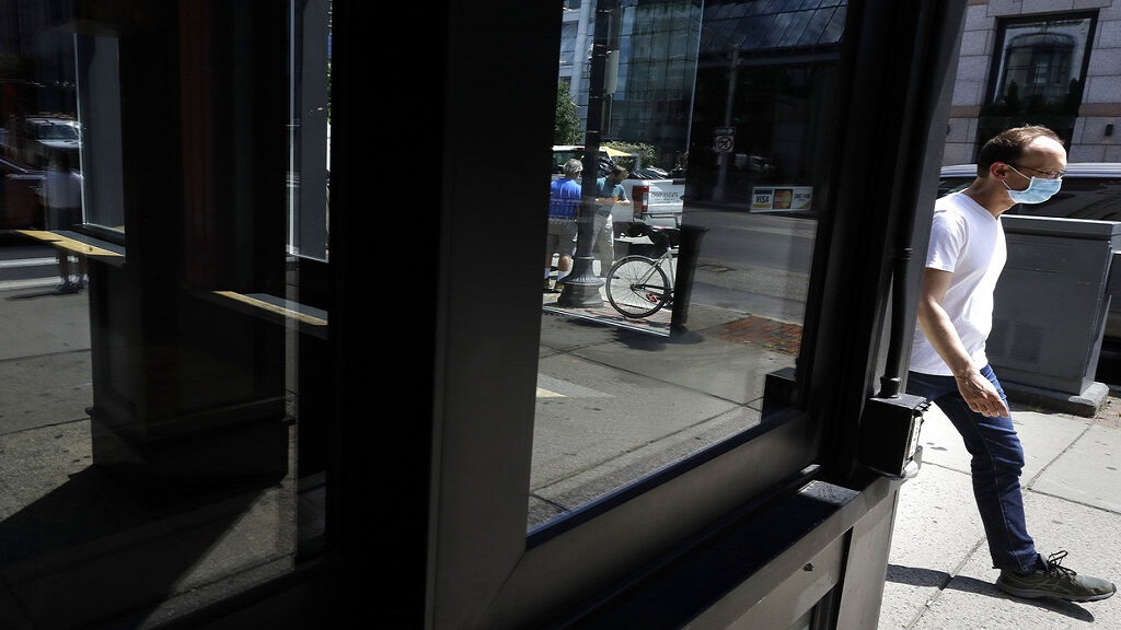 A passers-by, right, walks past a storefront window, Tuesday, July 28, 2020, in Boston. (AP Photo/Steven Senne)