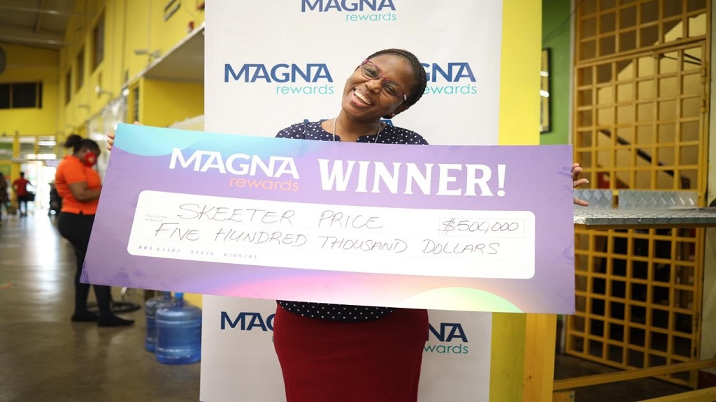An elated Skeeter Price triumphantly shows off her prize after being named the winner of the Win 500k the Scotiabank Magna Way promotion at Joong Supermarket in Portmore, St Catherine.