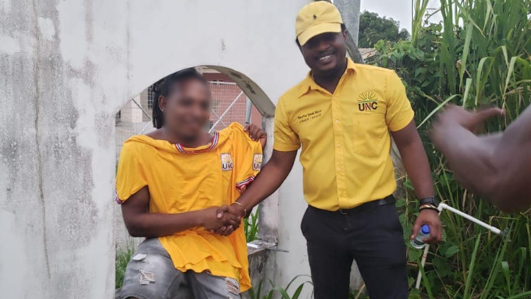 Photo: A supporter holds up a UNC tshirt and poses for a photo with the UNC's D'Abadie/O'Meara candidate Maurice Hoyte during a walkabout in Boys Lane and Extension, D'Abadie on July 15, 2020. Photo via Facebook, UNC- United National Congress.