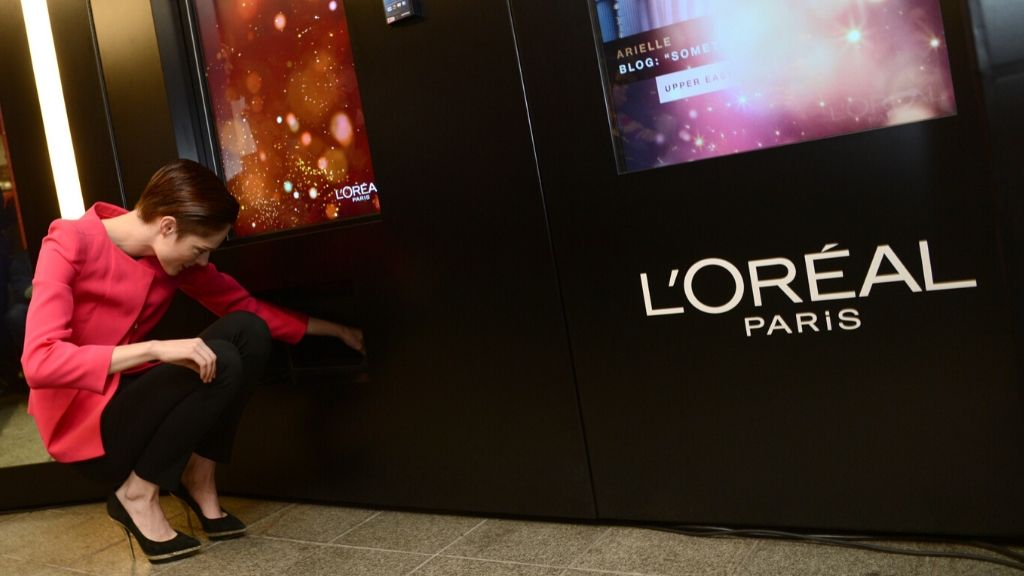 Model cum pose instructor Coco Rocha retrieves a token from a L'Oréal Paris vending machine.