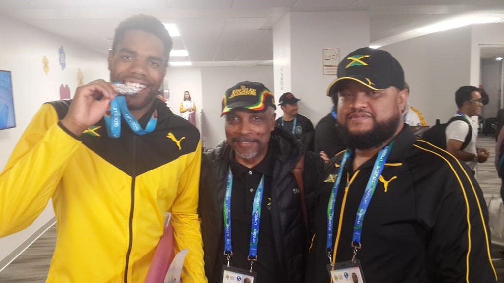 Diver Yona Knight-Wisdom (left) bites on his medal as he celebrates winning a historic silver in the men's 1m springboard competition at the Pan American Games in Lima, Peru, on Thursday, August 1, 2019. It was Jamaica's first ever medal in diving competition at the Pan Am Games. Sharing in the occasion are Christopher Samuda (centre), President, JOA and Ryan Foster, the JOA's CEO/General Secretary.