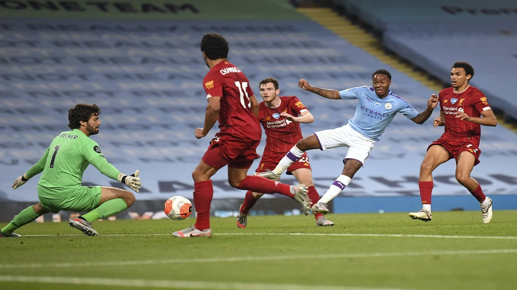 Manchester City's Raheem Sterling kicks the ball past Liverpool's goalkeeper  Alisson during their English Premier League football match between at the Etihad Stadium in Manchester, England, Thursday, July 2, 2020. (AP Photo/Laurence Griffiths,Pool).