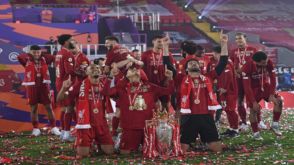 Fabinho, left, goalkeeper Alisson, right, and Roberto Firmino, all from Brazil, celebrate with the English Premier League trophy after Liverpool beat Chelsea 5-3 in their English Premier League football match at Anfield Stadium in Liverpool, England, Wednesday, July 22, 2020. The trophy was presented at the teams last home game of the season. (Laurence Griffiths, Pool via AP).
