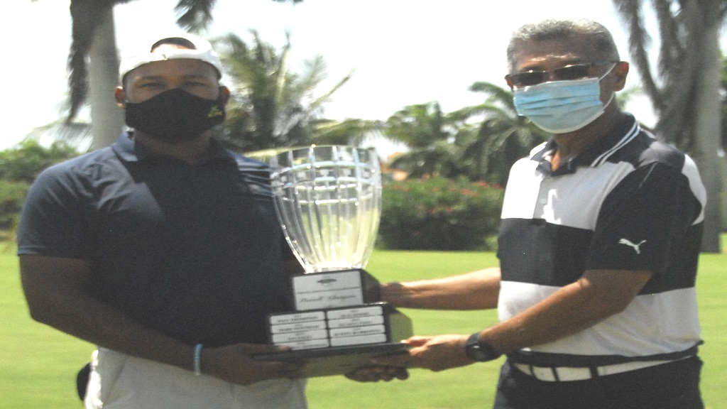William Knibbs (left) accepts the National Amateur Golf Championship trophy from Jamaica Golf Association president Peter Chin at the Half Moon Golf Course in Montego Bay on Sunday, July 19, 2020.