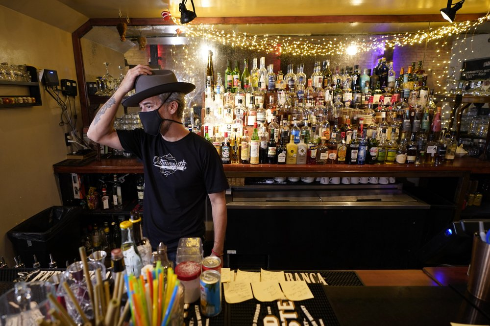 Michael Neff, co-owner of the Cottonmouth Club, adjusts his hat as he stands behind the bar. (AP Photo/David J Phillip)
