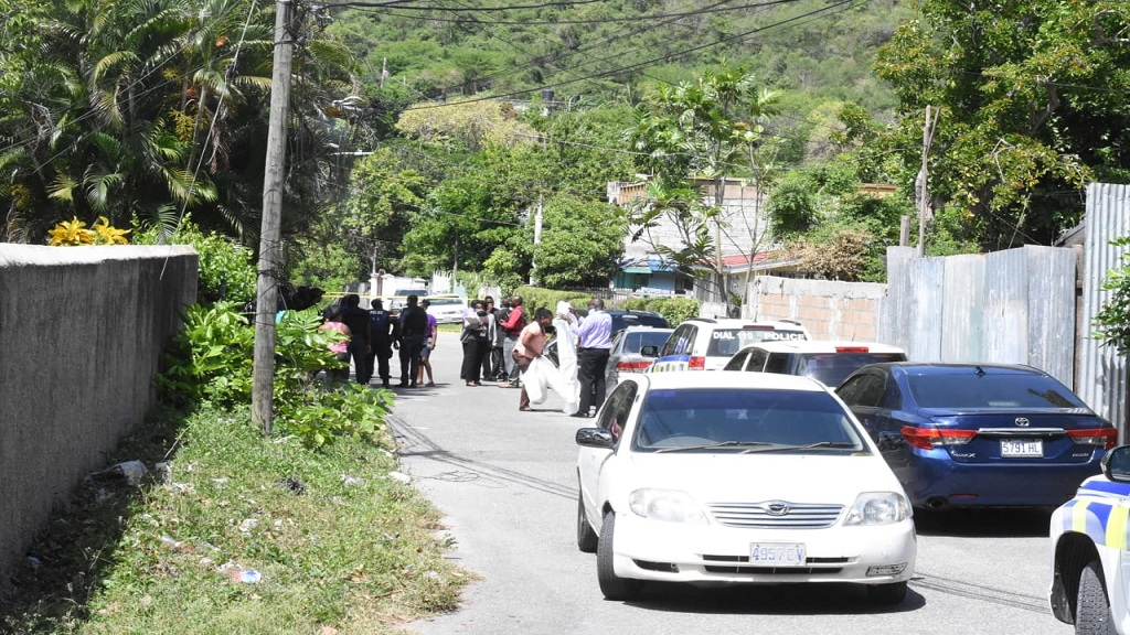 Police protest the crime scene in August Town where two men, said to be brothers, were shot dead on Wednesday morning. (Photo: Marlon Reid)