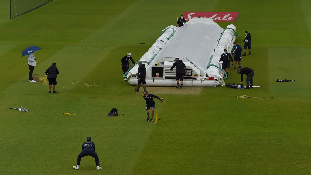 Groundsmen cover the pitch area before the start of the first day of the opening cricket Test match between England and West Indies, at the Ageas Bowl in Southampton, England, Wednesday July 8, 2020. (Mike Hewitt/Pool via AP).