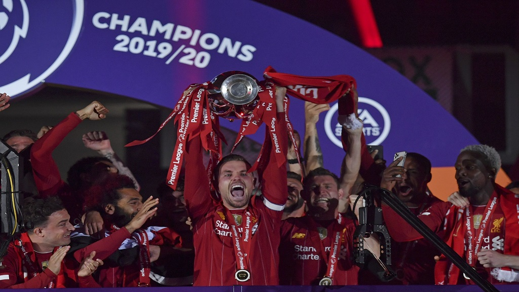 Liverpool's Jordan Henderson holds the English Premier League trophy aloft after it was presented following the Premier League football match against Chelsea at Anfield stadium in Liverpool, England, Wednesday, July 22, 2020. (Paul Ellis, Pool via AP).