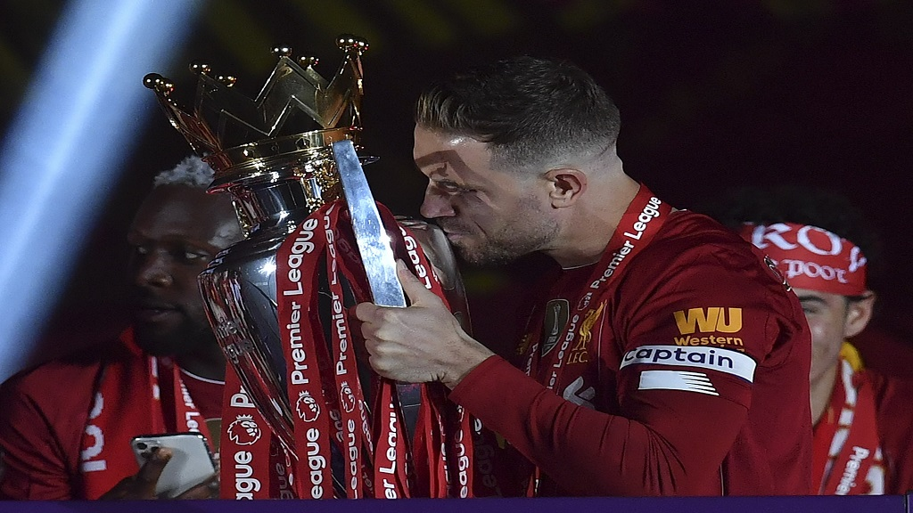 Liverpool captain Jordan Henderson kisses the English Premier League trophy after it was presented following the Premier League footall match against Chelsea at Anfield stadium in Liverpool, England, Wednesday, July 22, 2020. (Paul Ellis, Pool via AP).