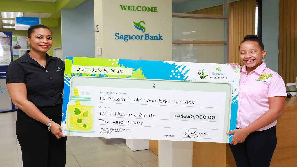 Marie Dowdie (left), Assistant Branch Manager, Sagicor Bank Jamaica Liguanea Branch, presents a symbolic cheque to 11-year-old Imani-Leigh Hall, founder of the ILAH's Lemon-Aid Stand for Kids Foundation, during a visit to the branch last Wednesday (July 8).