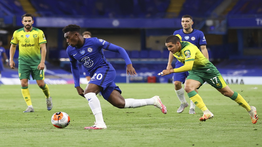 Chelsea's Callum Hudson-Odoi, centre, takes the ball away from Norwich City's Emi Buendia during the English Premier League football match at Stamford Bridge in London, England, Tuesday, July 14, 2020. (AP Photo/Julian Finney, Pool).