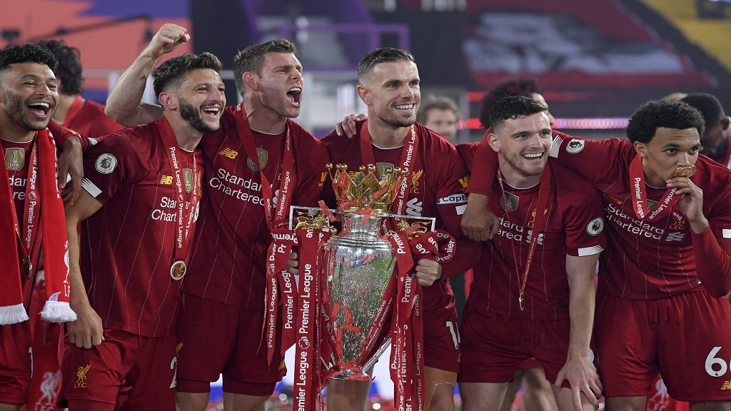 Liverpool players Alex Oxlade-Chamberlain, Adam Lallana, James Milner, Jordan Henderson, Andrew Robertson and Trent Alexander-Arnold celebrate with the English Premier League trophy after it was presented following their match against Chelsea at Anfield stadium in Liverpool, England, Wednesday, July 22, 2020. (Laurence Griffiths, Pool via AP).