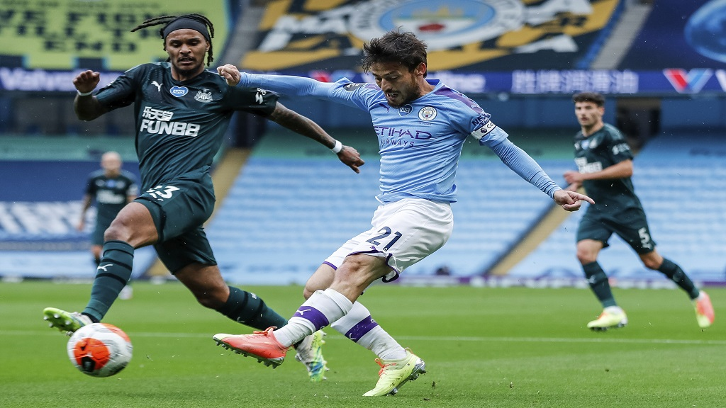 Manchester City's David Silva shots past Newcastle's Valentino Lazaro, left, during the English Premier League football match bagainst Newcastle at the Ethiad Stadium in Manchester, England, Wednesday, July 8, 2020. (Lee Smith/Pool via AP).