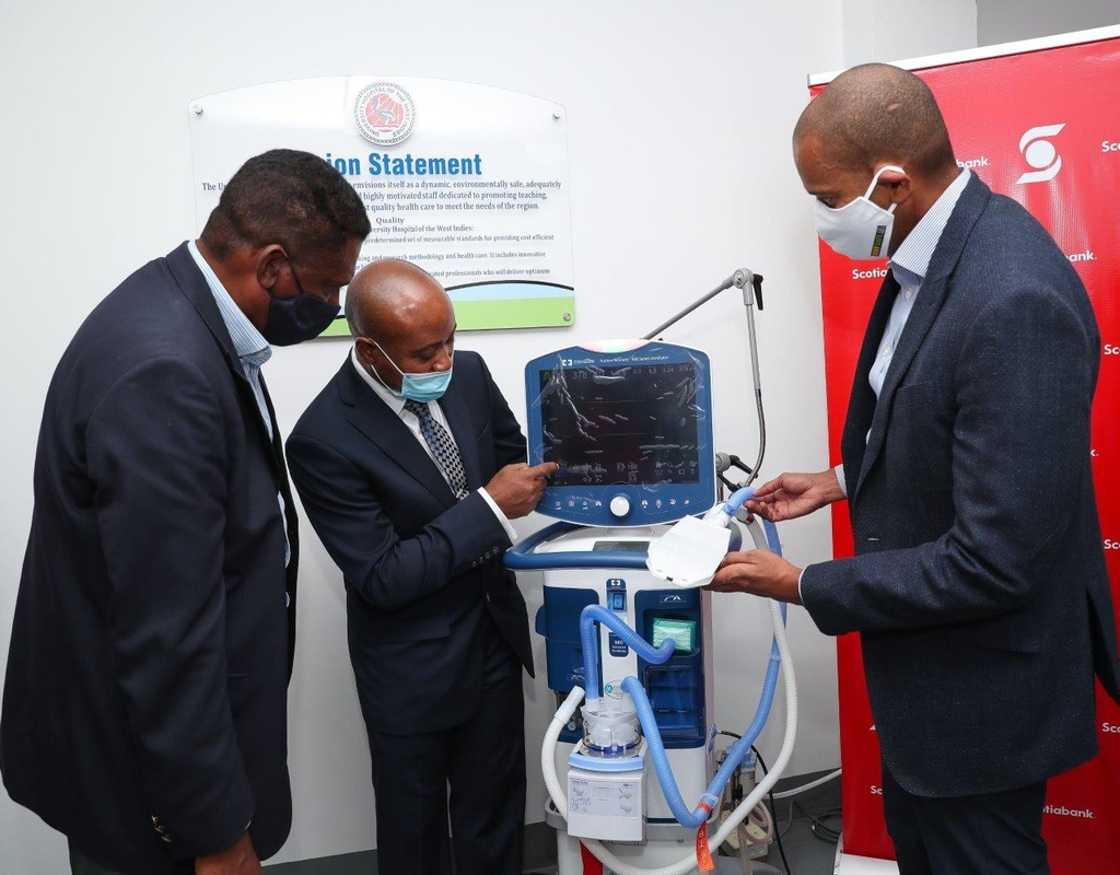 L-R: Courtney Cephas, Executive Director of the Health for Life and Wellness Foundation in the Ministry of Health and Wellness looks on as Dr Kelvin Metalor (centre), Intensive Care Unit ( ICU) Director at the University Hospital of the West Indies (UHWI) demonstrates the various functions of one of several newly donated ventilators to David Noel (right), President and CEO of Scotiabank during a presentation ceremony hosted at the hospital.
