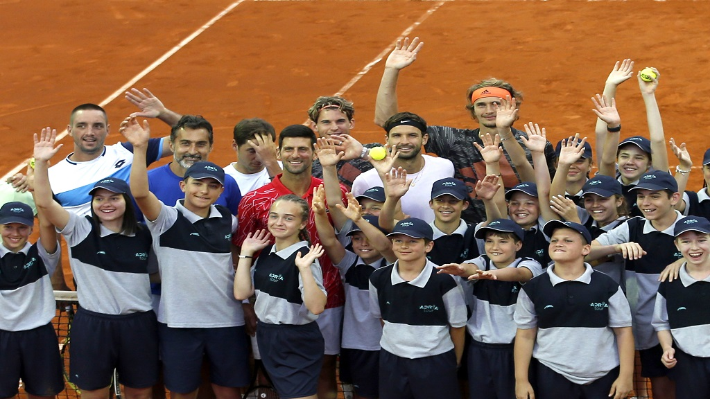 In this photo taken on Friday, June 12, 2020, Serbia's Novak Djokovic, centre, poses with volunteers and players during the Adria Tour charity tournament, in Belgrade Serbia. (AP Photo/Darko Vojinovic).
