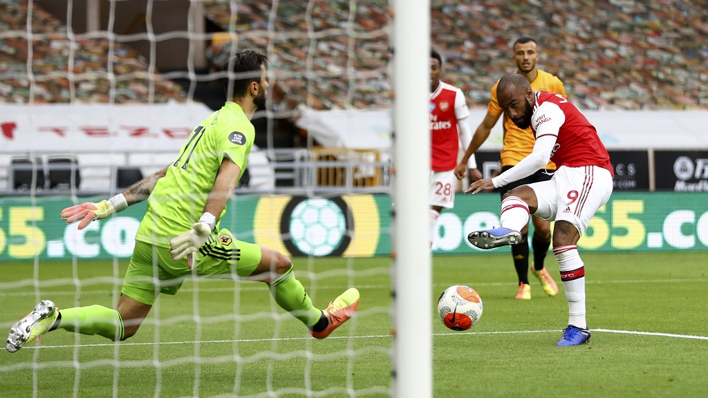Arsenal's Alexandre Lacazette scores his side's second goal past Wolves' goalkeeper Rui Patricio, left, during the English Premier League football match at the Molineux Stadium in Wolverhampton, England, Saturday, July 4, 2020. (Michael Steele/Pool via AP).