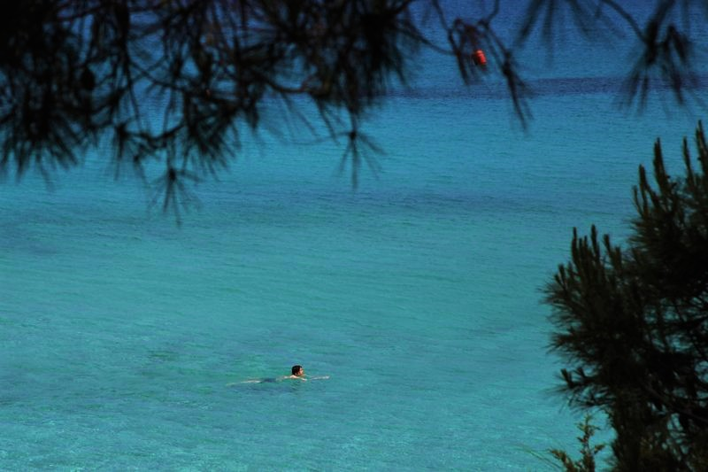 Sunday, May 10, 2020 photo, a lone swimmer wades through the clear waters of 'Konnos' beach in Ayia Napa, a seaside resort that's popular with tourists from Europe and beyond. (AP Photo/Petros Karadjias)