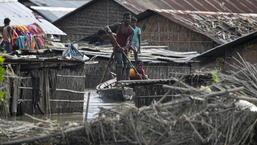 A flood affected family rides on a boat near their partially submerged house in Morigaon district, Assam, India, Thursday, July 16, 2020. Floods and landslides triggered by heavy monsoon rains have killed dozens of people in this northeastern region. (AP Photo/Anupam Nath)