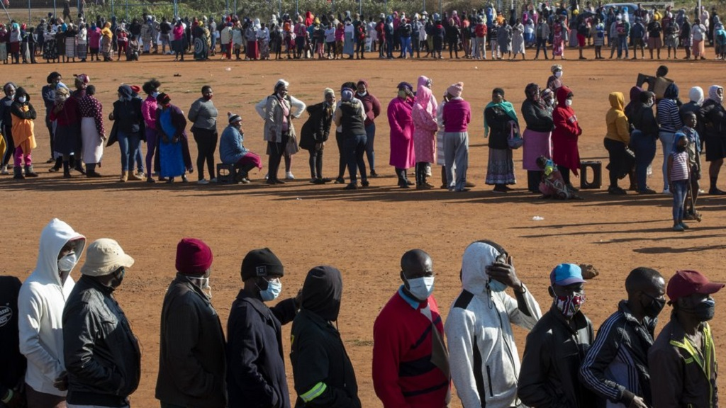 FILE — In this May 20, 2020 file photo, people affected by the coronavirus economic downturn line up to receive food parcels in Pretoria, South Africa. South Africa's COVID-19 response has been marred by corruption allegations around its historic dollars 26 billion economic relief package, as the country with the world's fifth highest number of COVID-19 cases braces for more. (AP Photo/Themba Hadebe/File)