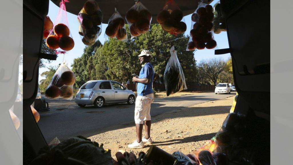 A man displays fruits and vegetables inside his car trunk while selling them by the side of a busy road in Harare, Zimbabwe. Cars have become mobile markets in Zimbabwe where enterprising residents are selling goods from their vehicles to cope with economic hardships caused by the coronavirus. With their car doors and trunks wide open by the side of busy roads, eager sellers display a colorful array of goods in Harare, the capital. (AP Photos/Tsvangirayi Mukwazhi)