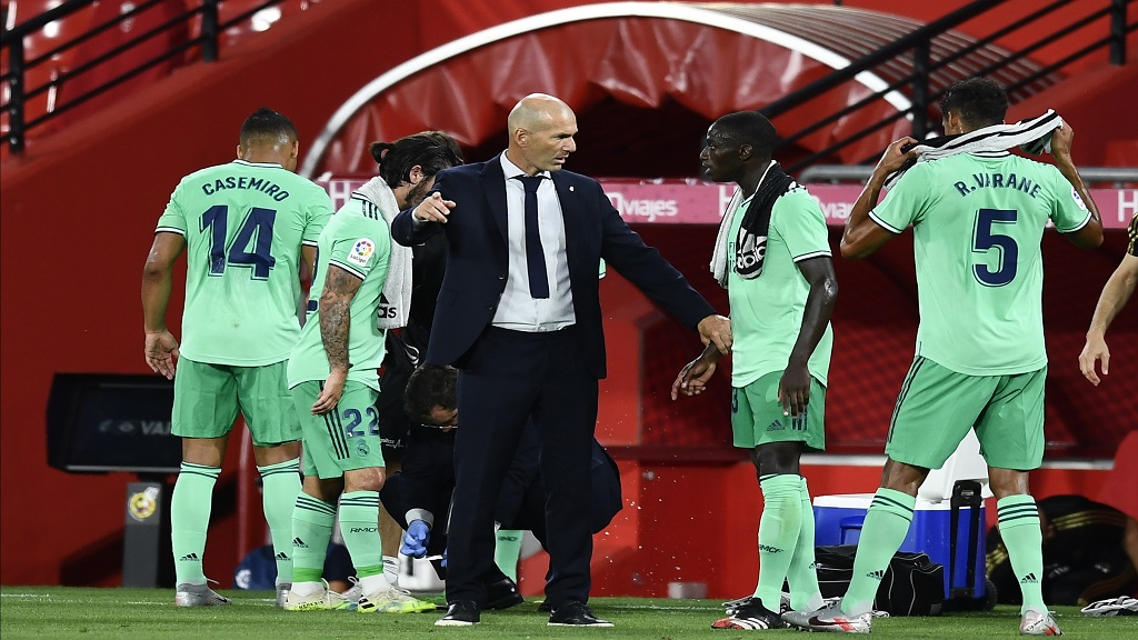 Real Madrid's head coach Zinedine Zidane talks with his players during the Spanish La Liga football match against Granada at the Los Carmenes stadium in Granada, Spain, Monday, July 13, 2020. (AP Photo/Jose Breton).