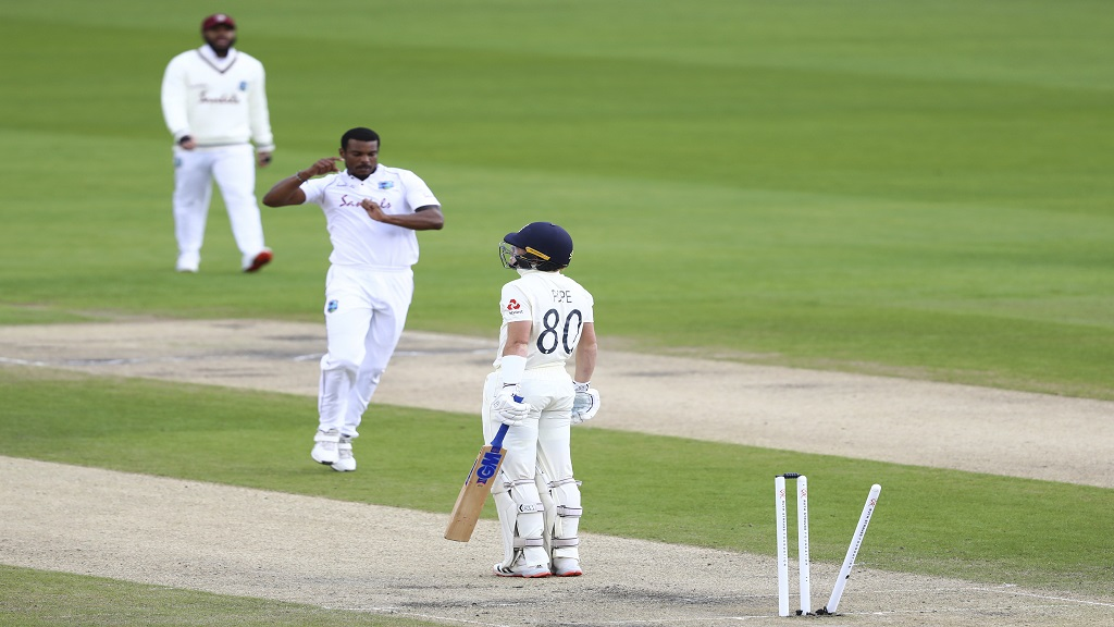 England's Ollie Pope, right, is bowled out by West Indies' Shannon Gabriel, centre, during the second day of the third cricket Test match at Old Trafford in Manchester, England, Saturday, July 25, 2020.(Michael Steele/Pool via AP).
