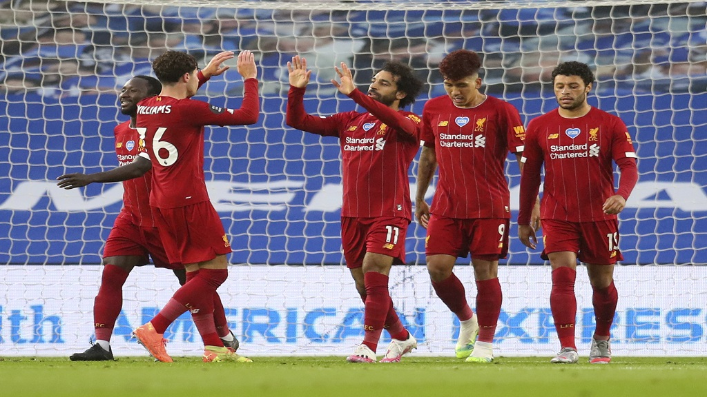 Liverpool's Mohamed Salah, centre, is congratulated by teammates after scoring his team's first goal during the English Premier League football match against Brighton at the Falmer Stadium in Brighton, England, Wednesday, July 8, 2020. (AP Photo/Catherine Ivill,Pool).