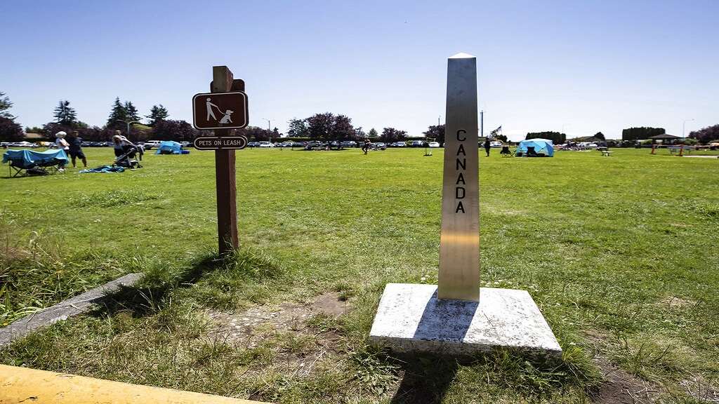 A Canada-US border marker stands in Surrey, British Columbia, as people gather at Peace Arch Historical State Park in Blaine, Wash., Sunday, July 5, 2020.