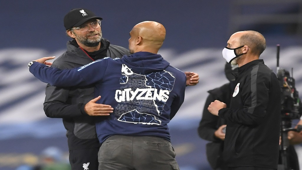 Liverpool's manager Jurgen Klopp, left, and Manchester City's head coach Pep Guardiola embrace after their English Premier League football match at the Etihad Stadium in Manchester, England, Thursday, July 2, 2020. (AP Photo/Laurence Griffiths,Pool).