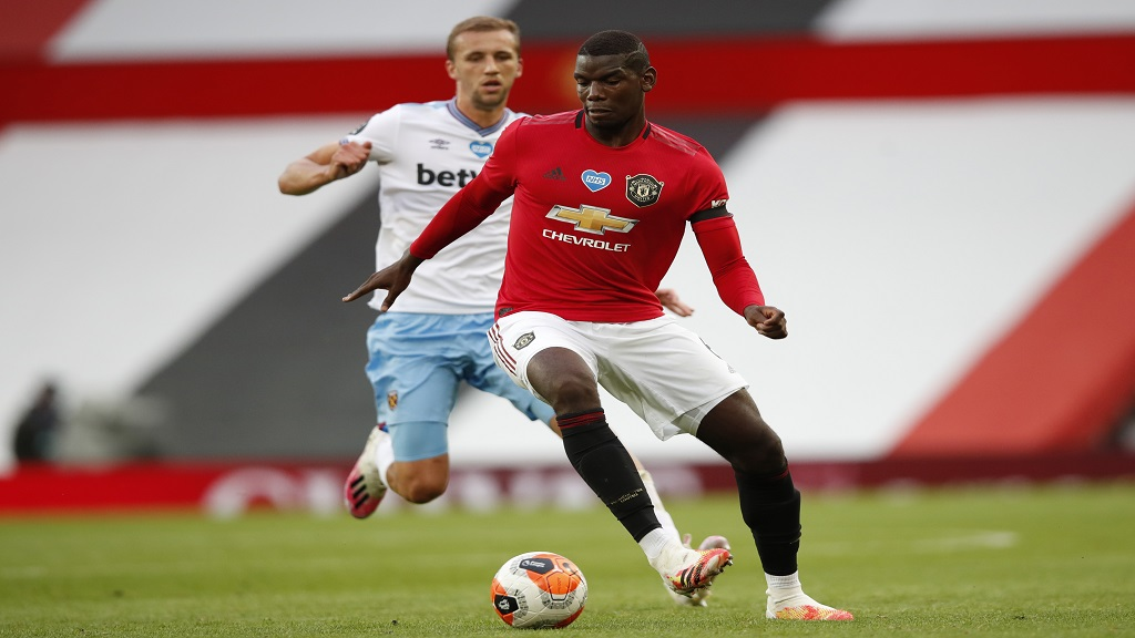Manchester United's Paul Pogba, centre, fights for the ball with West Ham's Tomas Soucek during the English Premier League football match at the Old Trafford stadium in Manchester, England, Wednesday, July 22, 2020. (Clive Brunskill/Pool via AP).