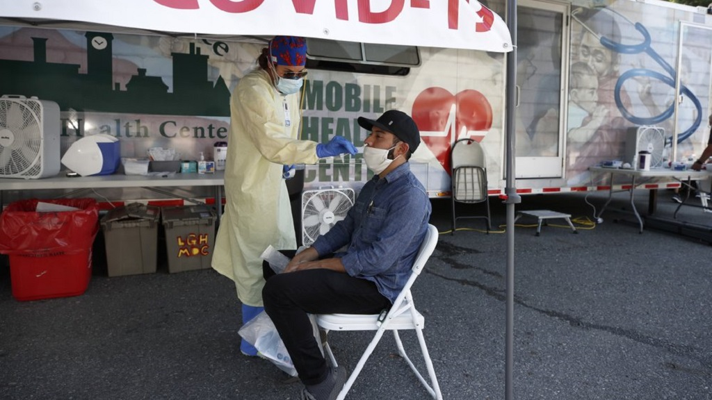 Nurse Tanya Markos administers a coronavirus test on patient Ricardo Sojuel at a mobile COVID-19 testing unit, Thursday, July 2, 2020, in Lawrence, Mass. (AP Photo/Elise Amendola)
