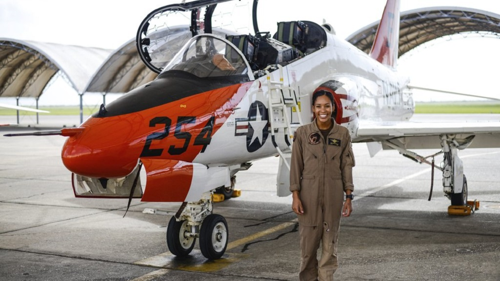 In this photo provided by the U.S. Navy, student Naval aviator Lt. j.g. Madeline Swegle, assigned to the Redhawks of Training Squadron (VT) 21 at Naval Air Station Kingsville, Texas, stands by a T-45C Goshawk training aircraft following her final flight to complete the undergraduate Tactical Air (Strike) pilot training syllabus, July 7, 2020, in Kingsville, Texas. (Lt.j.g. Luke Redito/U.S. Navy via AP)
