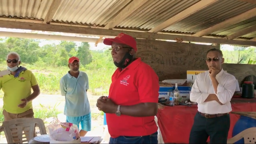 A listening Vasant Bharath (in white) stands behind Moruga/Tableland cadidate Winton 'Gypsy' Peters (in red) at a meeting in Moruga.