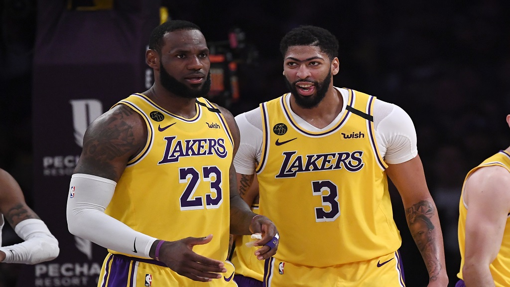 In this Feb. 21, 2020, file photo, Los Angeles Lakers forward LeBron James, left, stands with forward Anthony Davis during the second half of an NBA basketball game against the Memphis Grizzlies in Los Angeles. James and Davis had the Lakers on course to contend for another NBA title before the coronavirus pandemic upended their first season together. AP Photo/Mark J. Terrill, File).