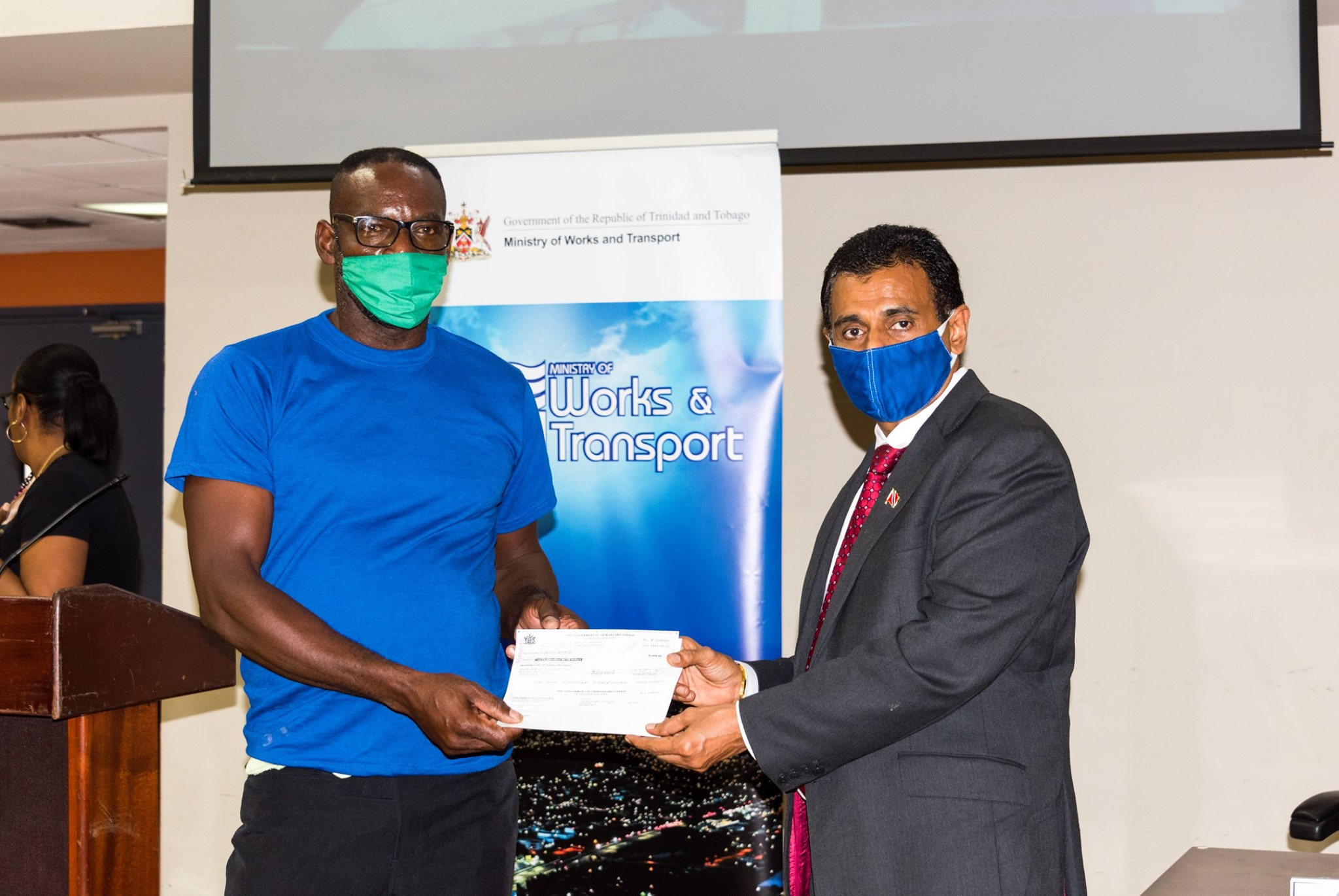 Minister of Works and Transport, Rohan Sinanan (right), hands over a $2,000 cheque to the owner of a maxi taxi. (via MOWT)