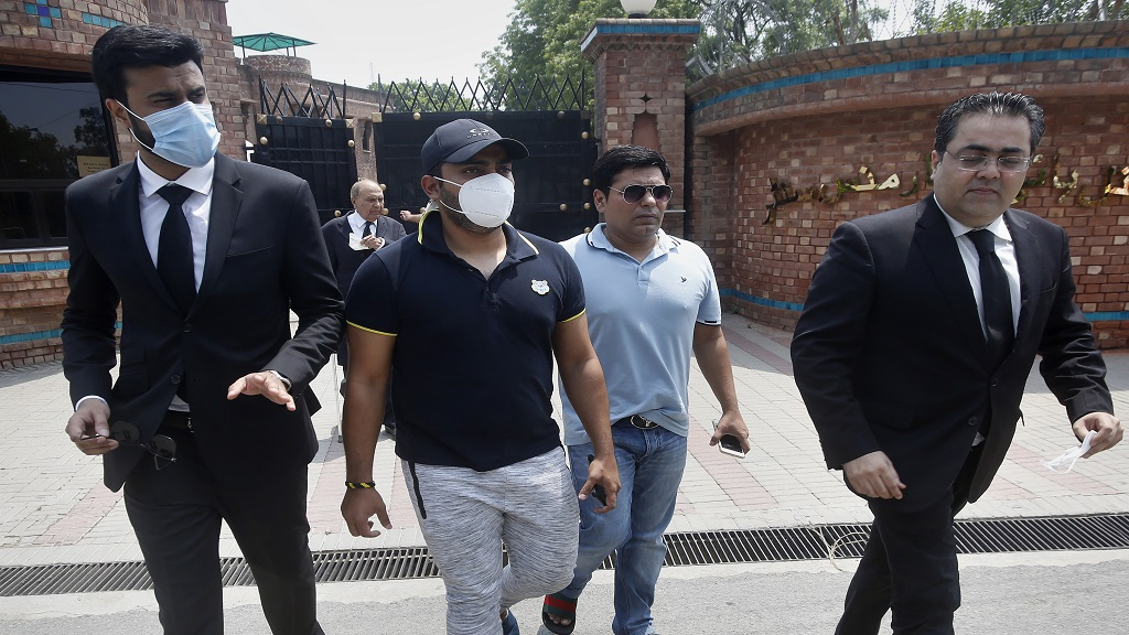 Pakistani cricketer Umar Akmal, centre, arrives with his lawyers at the Pakistan Cricket Board office in Lahore, Pakistan, Wednesday, July 29, 2020.  (AP Photo/K.M. Chaudhry).