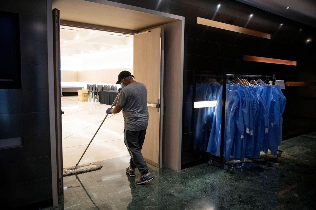 Un employé nettoie le sol de l'hôtel Melia Barcelona Sarria alors que l'hôtel a été transformé en une structure médicale pour traiter les cas les moins graves de coronavirus à Barcelone .