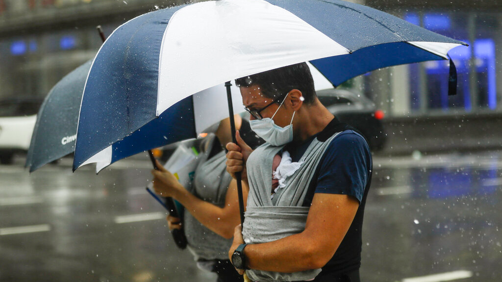 A man uses an umbrella to protect a baby from inclement weather brought about by Tropical Storm Fay, Friday, July 10, 2020, in New York. Beaches closed in Delaware and rain lashed the New Jersey shore as fast-moving Tropical Storm Fay churned north on a path expected to soak the New York City region. (AP Photo/Frank Franklin II)