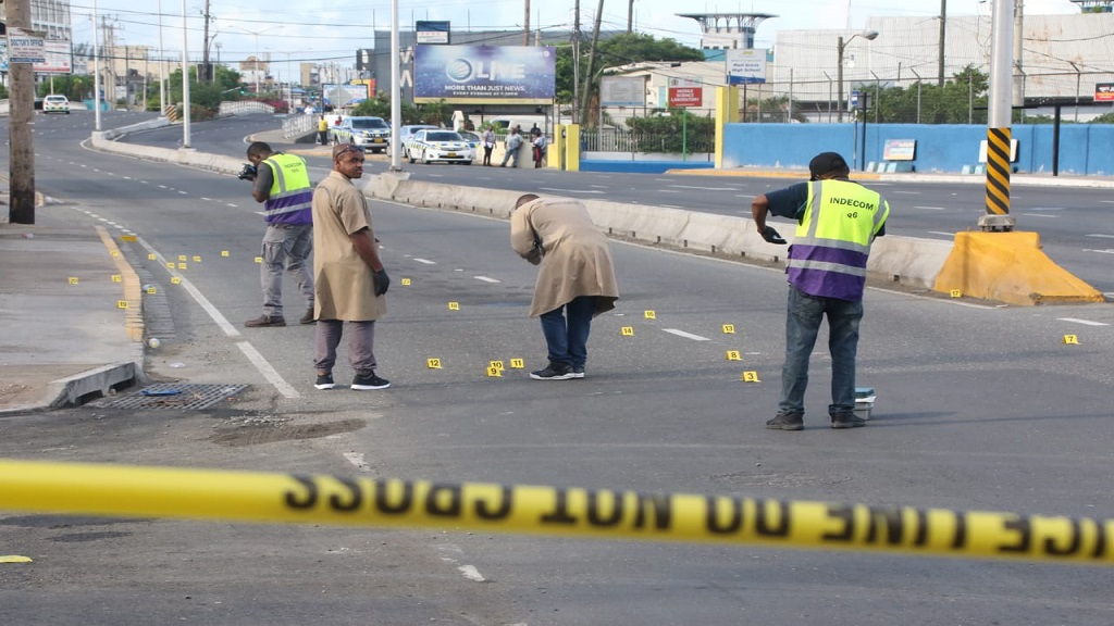Police and INDECOM# personnel investigating the scene of the gun battle between criminals and a police team on Constant Spring Road in St Andrew early Thursday morning.