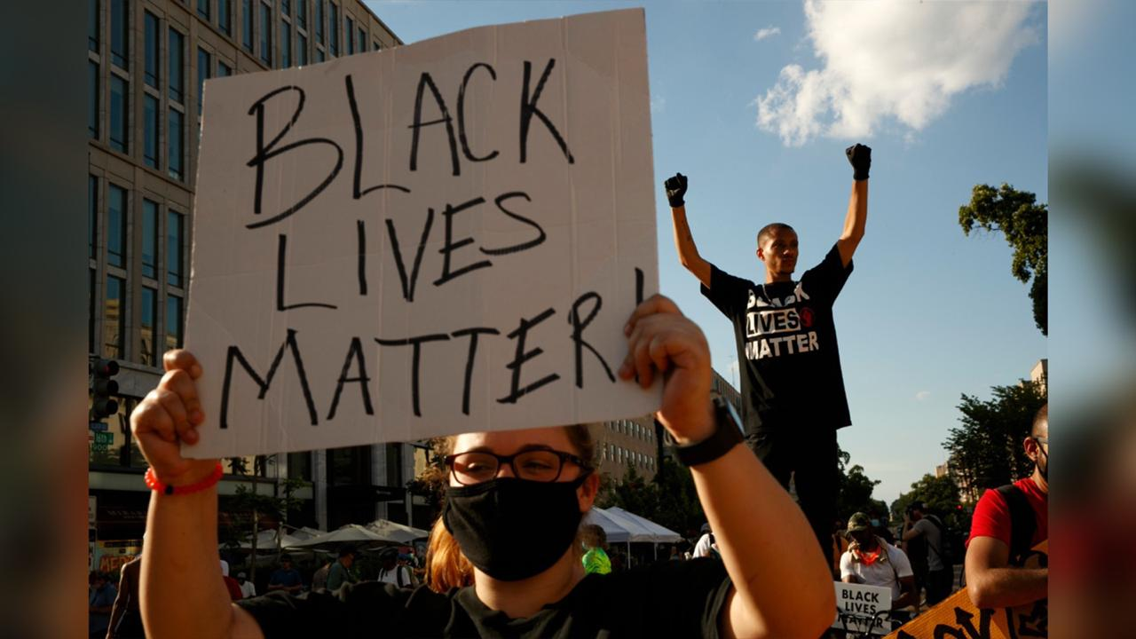 In this June 24, 2020, file photo, Antonio Mingo, right, holds his fists in the air as demonstrators protest in front of a police line on a section of 16th Street that's been renamed Black Lives Matter Plaza, in Washington. Thousands of Black activists from across the U.S. will hold the 2020 Black National Convention on Aug. 28, 2020, via livestream to produce a new political agenda that builds on the protests that followed George Floyd's death. (AP Photo/Jacquelyn Martin, File)