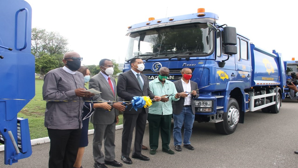 Prime Minister Andrew Holness (centre) leads the ribbon cutting ceremony for the handing over of 20 garbage trucks to the NSWMA.