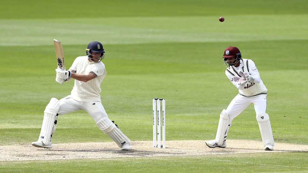 England's Ben Stokes, left, plays a shot during the second day of the second cricket Test match against West Indies at Old Trafford in Manchester, England, Friday, July 17, 2020. (Michael Steele/Pool via AP).