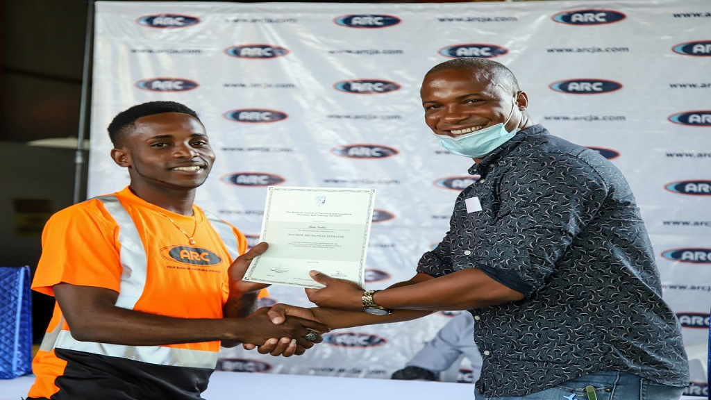 Rian Forbes (left) beamed with pride as he accepted his certificate from Acting General Manager - Technical Division, Levar Beezer (right).